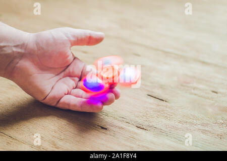 A man hand holding hand spinner or fidget spinner over wooden background. - Stock Photo
