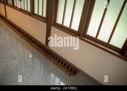Leather slippers in row inside buddhist temple - Stock Photo