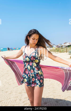 Woman at the beach holding sarong up in the air - Stock Photo