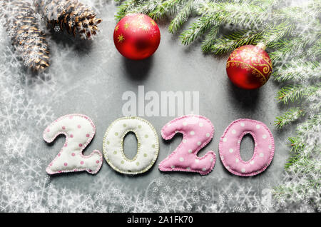 Colorful stitched digits 2020 of polkadot fabric with Christmas decorations flat lay on stone background - Stock Photo