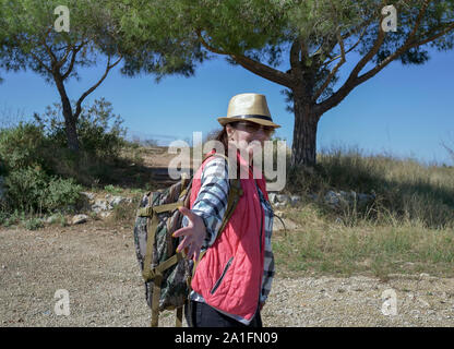 Happy girl tourist walks along a mountain trail turns around and holds out his hand, follow me - Stock Photo