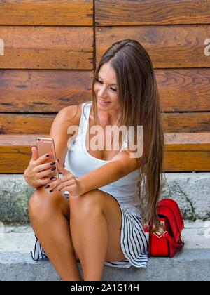 Attractive young woman looking down into camera cellphone making selfie sitting on entrance porch doorstep before wooden doors door - Stock Photo