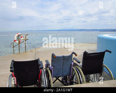 Wheelchairs on an accessible beach for transportation of people with disabilities in the water. - Stock Photo