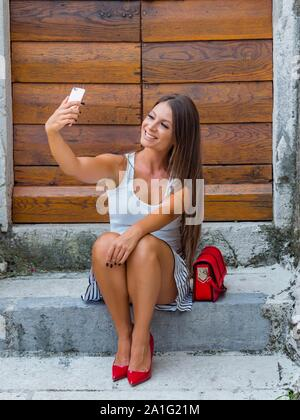 Female legs heels looking up into camera cellphone taking selfie sitting on entrance porch doorstep before wooden doors door color vertical - Stock Photo