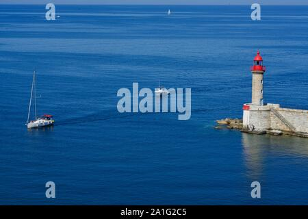 Two boats passing a lighthouse - Stock Photo