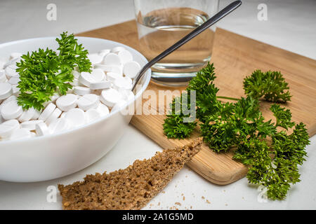 plate filled with medical pills drugs is on the table with a spoon inside, next to the food: green parsley on a cutting board, rye bread and a glass o - Stock Photo