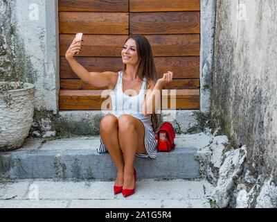 Female legs in heels looking up into camera cellphone sitting on entrance porch doorstep before wooden doors door color horizontal highheels - Stock Photo