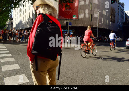 People waiting for a traffic light in red while cyclists pass through a downtown street. Barcelona, Catalonia, Spain. - Stock Photo