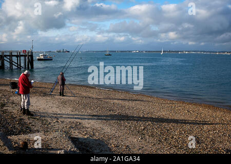 A man wearing a red coat stood on Calshot Beach next to the Solent in the English Channel while a fisherman sets up ready for a days fishing