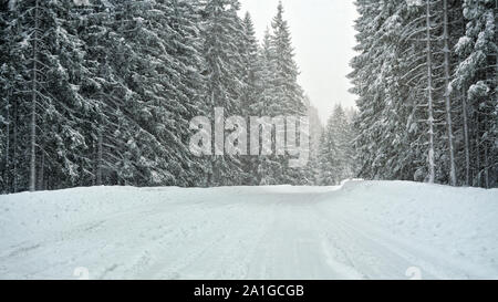 Forest road completely covered with snow in winter, trees on both sides. Slippery ground - dangerous driving conditions - Stock Photo