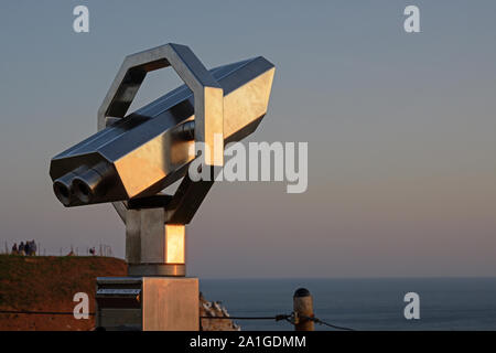 Public telescope to watch the birds at a vantage point on the cliffs of Heligoland during sunset, copy space - Stock Photo