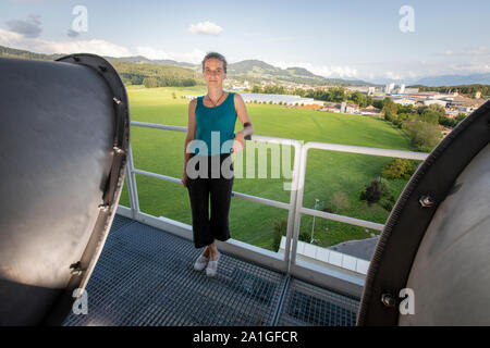 Louise Charles at Climeworks next to a DAC 18 unit. The Swiss company Climeworks are running 30 DAC - Direct Air Capture - fans on the roof of this garbage incinerator in Hinwil outside Zurich. Founded in 2009 by Christoph Gebald and Jan Wurzbacher, the company has commercialized the modular carbon capture unit, each of which is capable of sucking up to 135 kilo of CO2 out of the air daily. The process is energy demanding, and the units in Hilwil get the power from the incinerator. In turn, the CO2 is pumped to neighboring greenhouses to accellerate the production of tomatoes and cucumbers. - Stock Photo