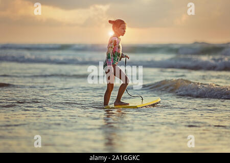 young surfer ride on surfboard with fun on sea waves. Stock Photo
