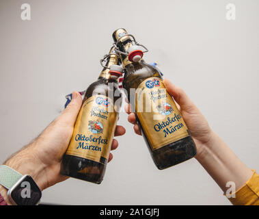 Munich, Germany - Mar 3, 2019: Male hand holding traditional Oktoberfest Marzen Pills beer against white background - Stock Photo