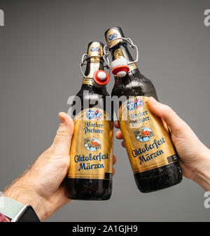 Munich, Germany - Mar 3, 2019: Close-up of man and woman hand holding drinking open bottle of traditional Oktoberfest Marzen Pills Hacker Pschorr beer against gray background - Stock Photo