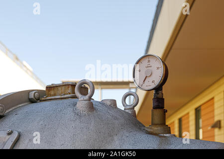 Old rusty damaged metal meter, valve tube system and gas or liquid tank for industry. Detail of broken circular measurement meter with rusty dial. - Stock Photo