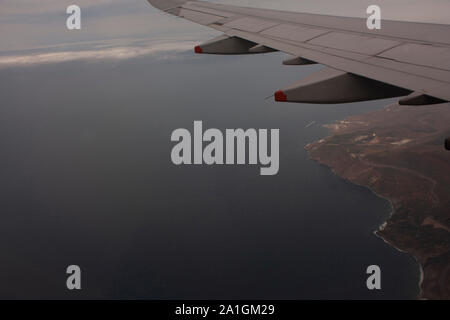 Landscape Aerial shot of earth and sea chain clouds and Mexican land approaching Tijuana Mexico - Stock Photo