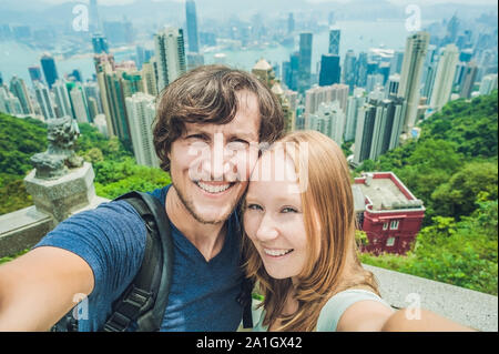Caucasian couple in Hong Kong. Young people taking selfie picture at viewpoint of famous attraction Victoria Peak, HK, China. - Stock Photo