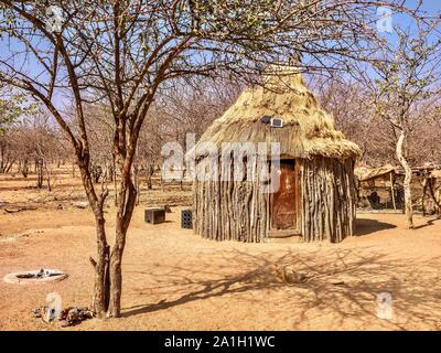 A traditional style African house in rural Namibia combined with modern technology. Walls are made of branches and mud, but small solar panels sit on - Stock Photo