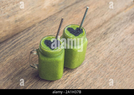 Fresh green smoothie with banana and spinach with heart of sesame seeds. Love for a healthy raw food concept. - Stock Photo