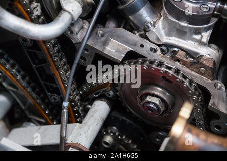 Close-up on a disassembled engine with a view of the gas distribution mechanism, chain, gears and tensioners during repair and restoration after a bre - Stock Photo