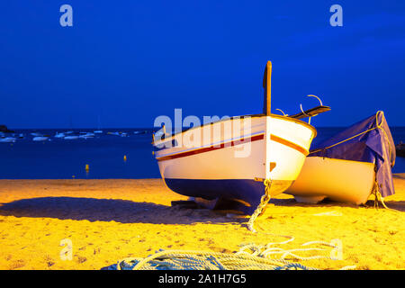 Two fishing boats on a sandy beach in the evening against the background of the sea. Lighting from lanterns, seashore in the Spanish city of Tossa de - Stock Photo