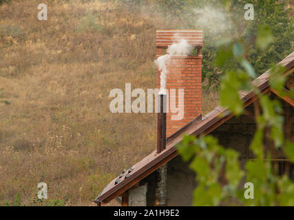 Smoke from chimney on roof of the house. - Stock Photo