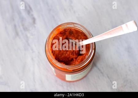Ajvar in a jar, a delicious roasted red pepper and eggplant dish/ Ajvar - traditional Macedonian Serbian dish made from red bell peppers, eggplant - Stock Photo