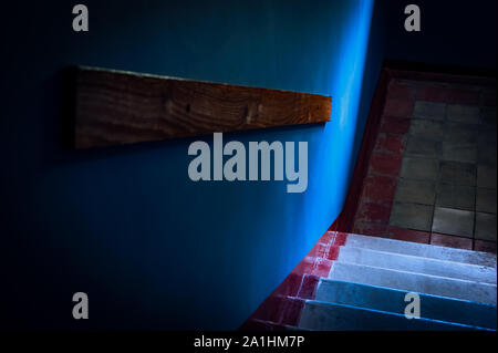 Top-Down View of Concrete Stairs, Wall Mounted Wooden Handrail in a Building Block. Cold Blue Light Spot from the Window. - Stock Photo