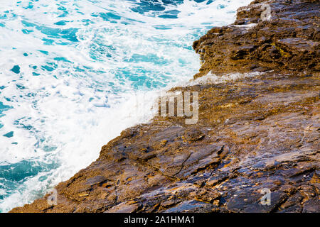 Nature blue turquoise sea vacation background with foam and waves on stone beach shore close up - Stock Photo