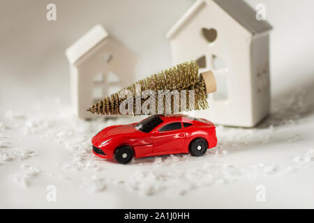 Christmas holiday concept with bright christmas tree on red toy car and snow around it. - Stock Photo