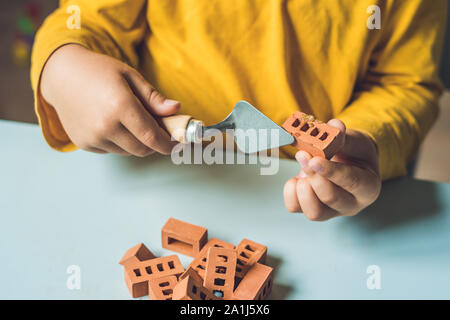 Close up of child's hands playing with real small clay bricks at the table. Toddler having fun and building out of real small clay bricks. Early learn - Stock Photo