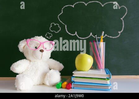Cute teddy bear wearing glasses next to a pile of books and an apple in a classroom. Drawn thought bubble on a blackboard with empty copy space - Stock Photo