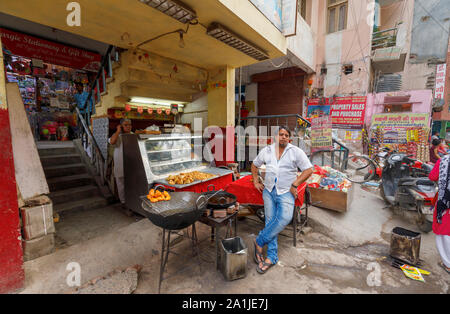 Street scene in Mahipalpur district, a suburb of New Delhi, capital city of India: roadside deep fried street food, samosas and pies, and seller - Stock Photo