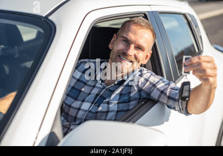 A man in a white car shows a key. - Stock Photo