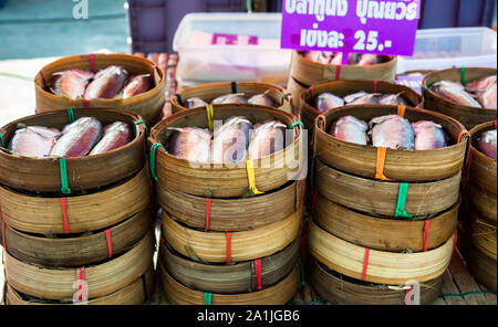 Fresh fish pre-packaged in steamers at the local market. Pakse, Laos - Stock Photo
