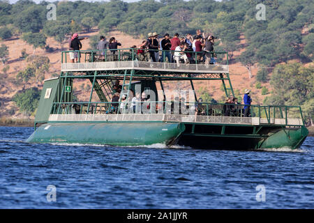 Tourists and photographers exploring wildlife from a river boat on the River Chobe, near Kasane in Botswana - Stock Photo