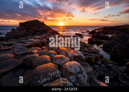 sunset over basalt columns Giant's Causeway known as UNESCO World Heritage Site, County Antrim, Northern Ireland - Stock Photo