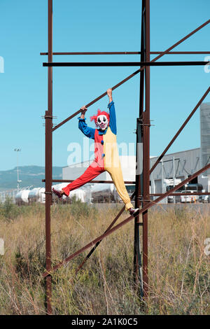a scary evil clown wearing a colorful yellow, red and blue costume outdoors, hanging from the rusty structure of an abandoned billboard - Stock Photo