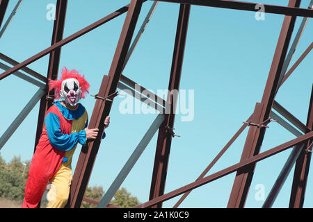 a scary evil clown, wearing a colorful yellow, red and blue costume outdoors, sticking out his tongue while hanging from the rusty structure of an aba - Stock Photo