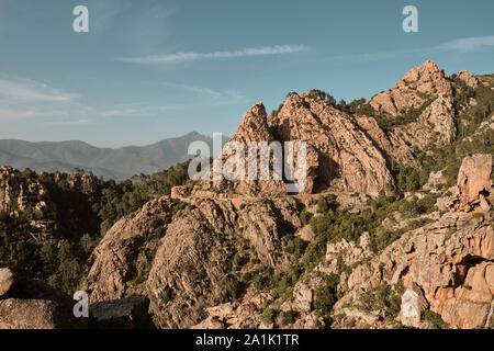 The red granite rocks and cliffs and road along the UNESCO World Heritage Site coastline of the Calanques de Piana / Gulf of Porto in western Corsica. - Stock Photo