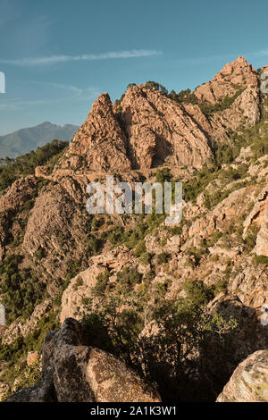The red granite rocks and cliffs and D81 road along the UNESCO World Heritage Site of the Gulf of Porto coast in western Corsica. - Stock Photo
