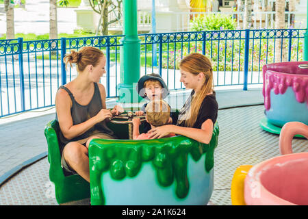 Happy mothers and little sons riding on a merry-go-round carousel together, smiling and having fun at a fair or amusement park. Active family leisure - Stock Photo