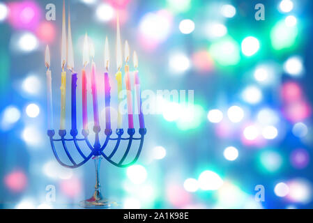 Image of jewish holiday Hanukkah on happy colorful background with menorah traditional candelabra and burning candles. - Stock Photo