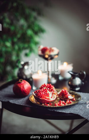 Still life composition with juicy red cut cleared pomegranate on a copper plate, burning candles and other oriental decor on the black table. Soft sel - Stock Photo