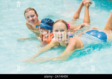 Happy young two women And boy playing and having a good time at water fun park pool, on a summer hot day. - Stock Photo