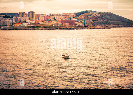 golden view of solitary small boat fishing in the Atlantic Ocean - Stock Photo