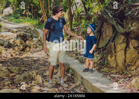 Father and son are walking along the forest road. - Stock Photo