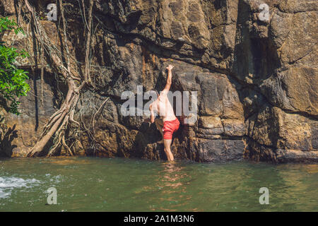 A man climbs up a mountain from the water. - Stock Photo