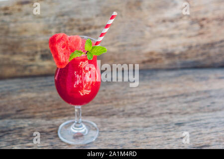 Healthy watermelon smoothie with mint and striped straws on a wood background. - Stock Photo